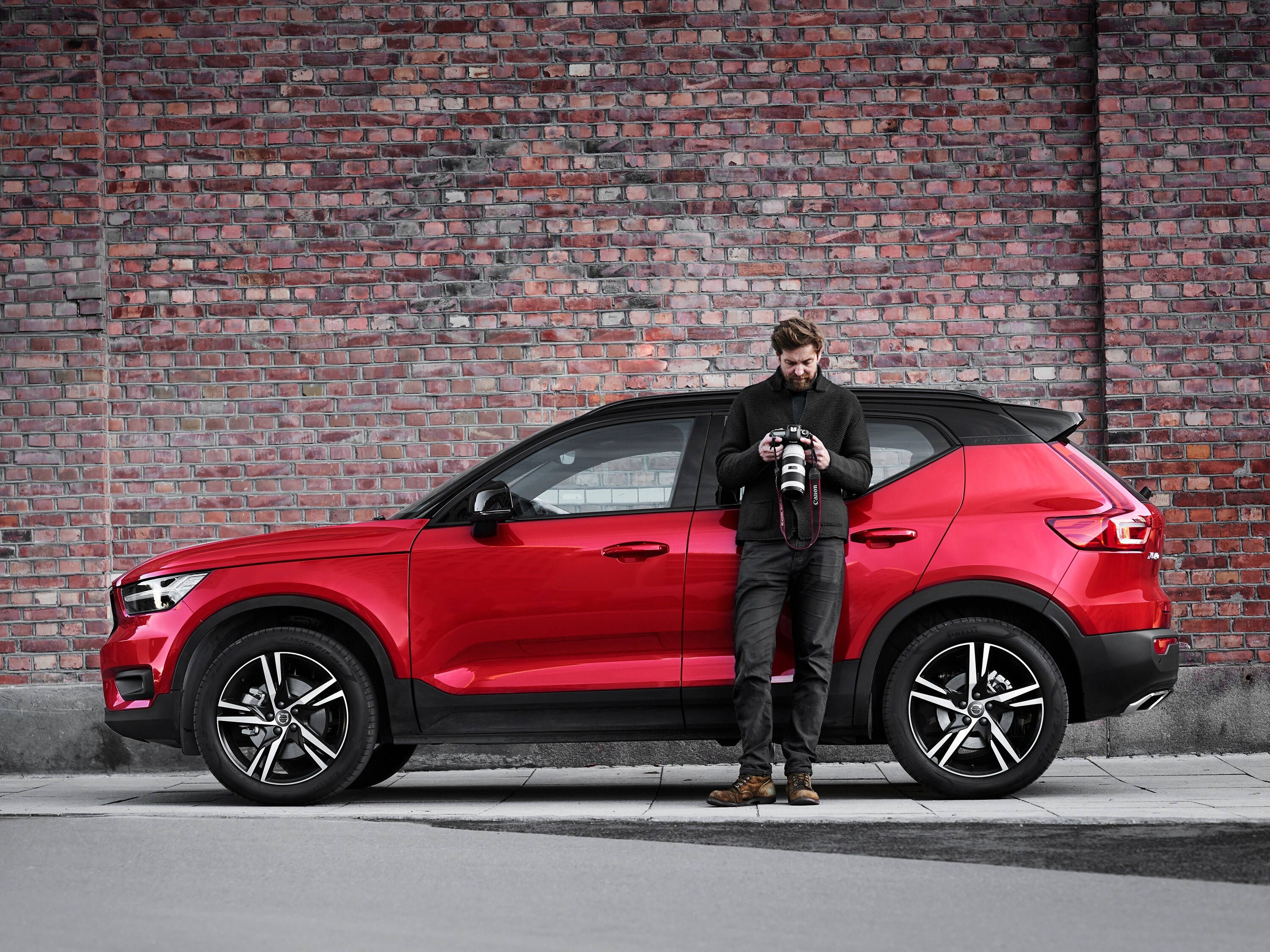 Photographer Sam Christmas leans against the side of a Volvo XC40 in Oslo, inspecting his camera