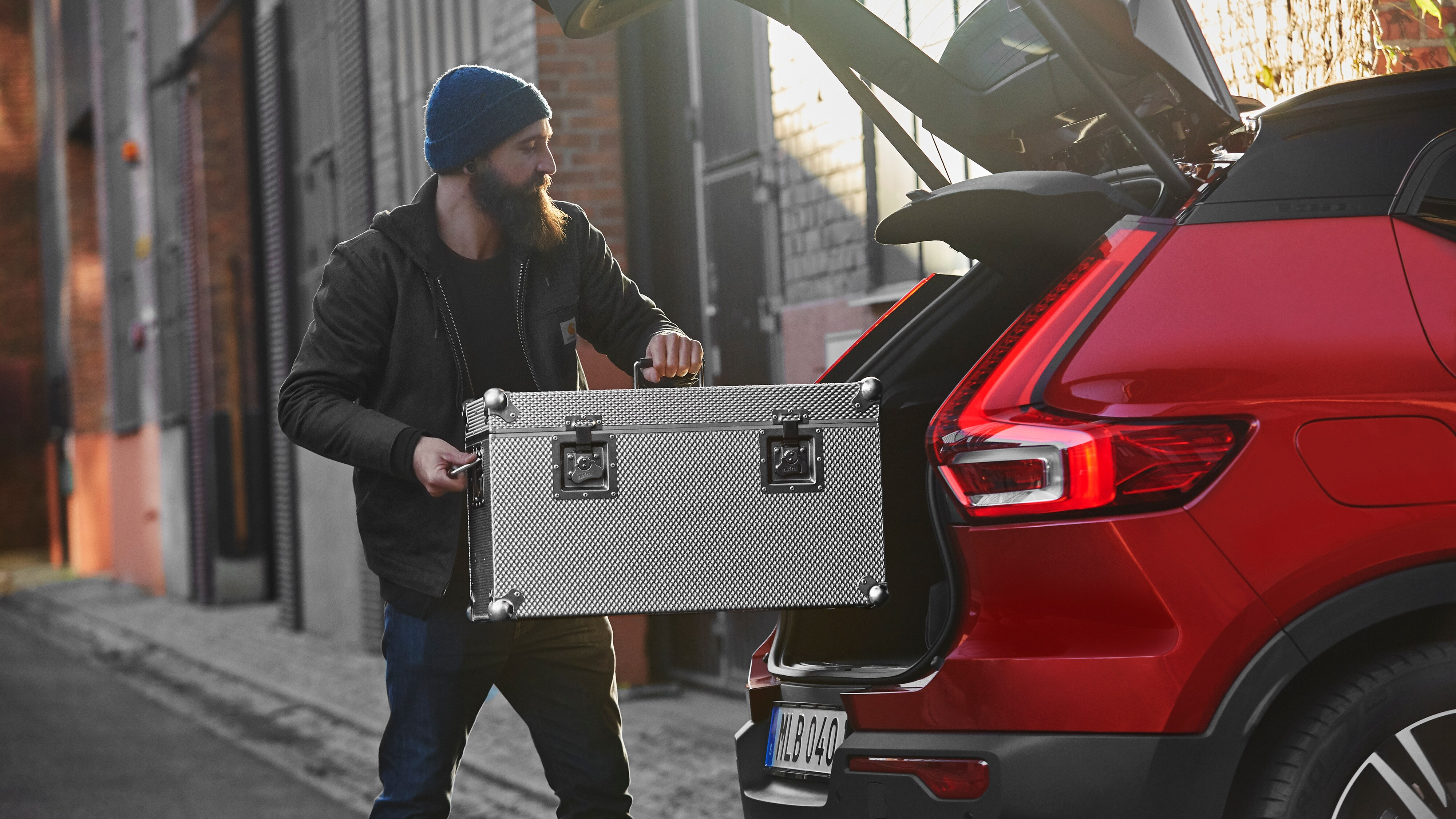 Photography Assistant Bruce Horak loads a large case of photography equipment into the trunk of a Volvo XC40