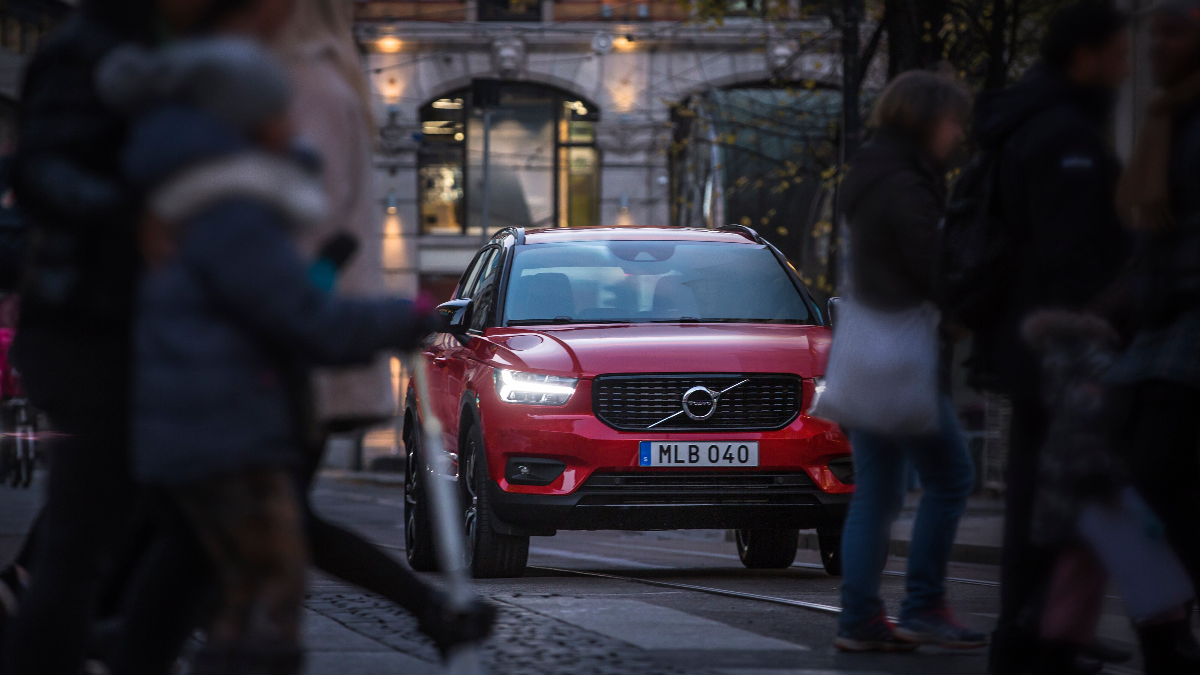 A Volvo XC40 stopped in the street in Oslo as pedestrians cross the road in foreground