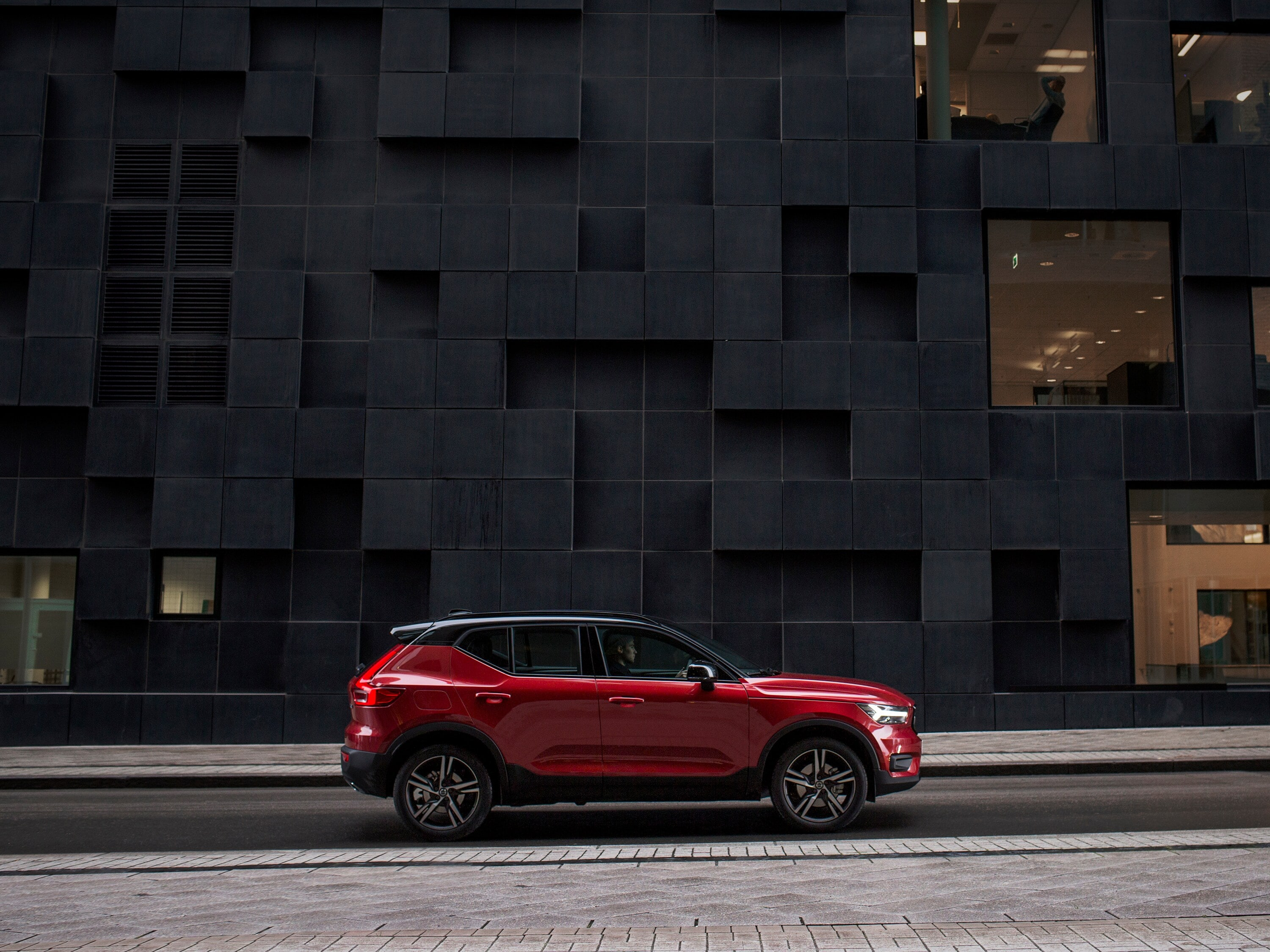 A Volvo XC40 drives down a street in front of a square-blocked building in Oslo