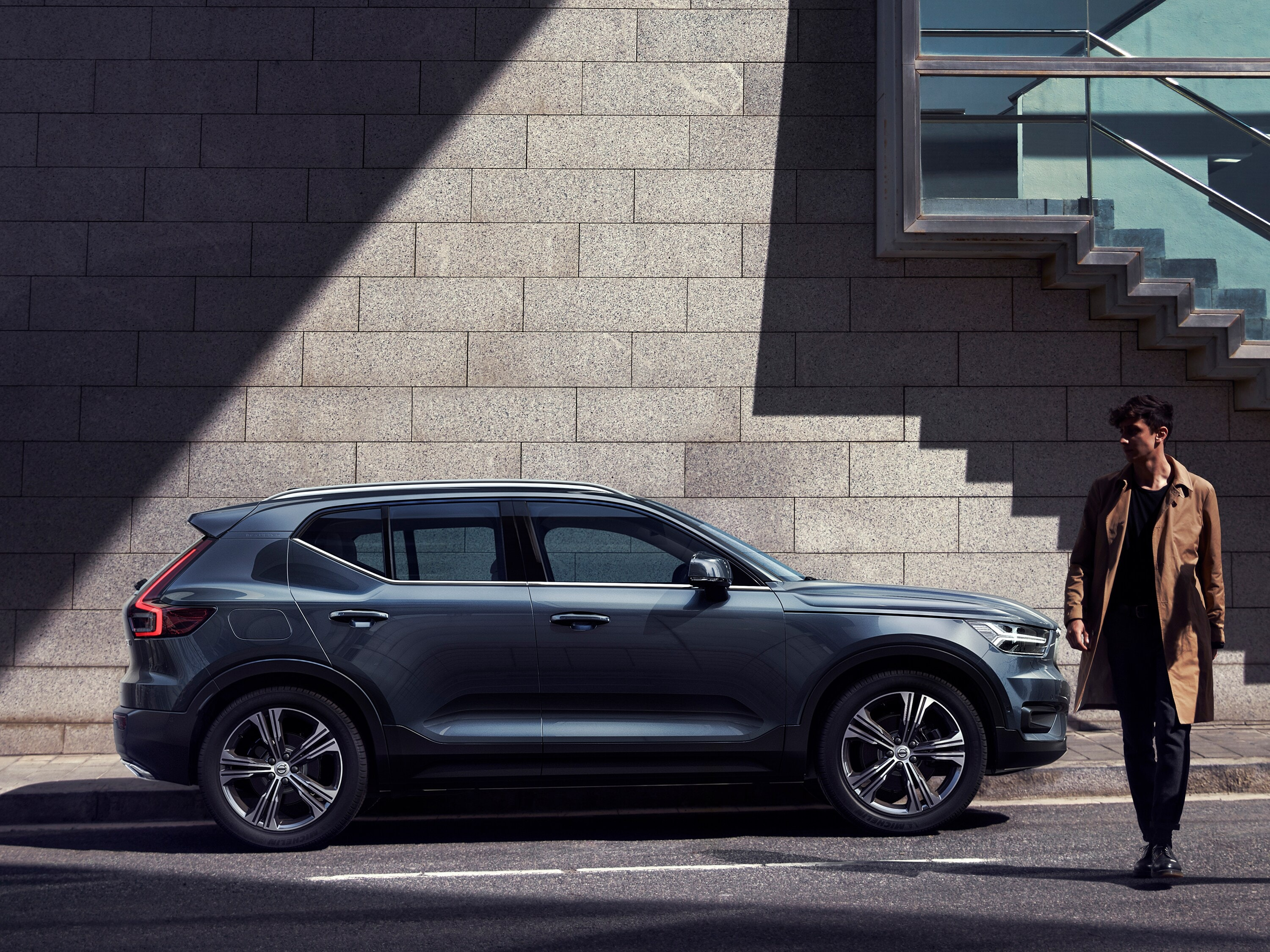 A man and woman cross the road in front of a parked Volvo XC40
