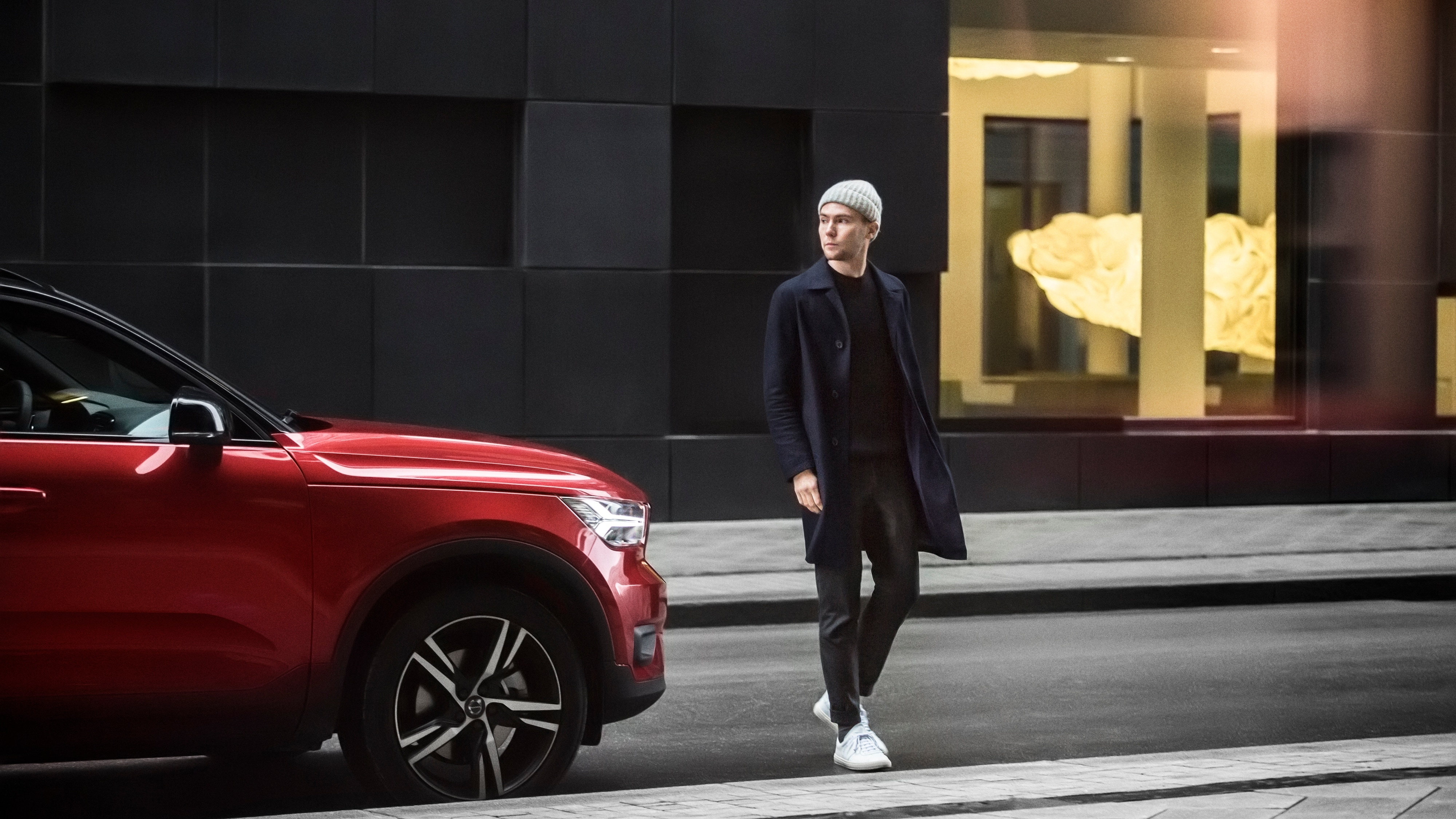 Norwegian style blogger Fredrik Risvik crosses a road in Oslo in front of a parked Volvo XC40