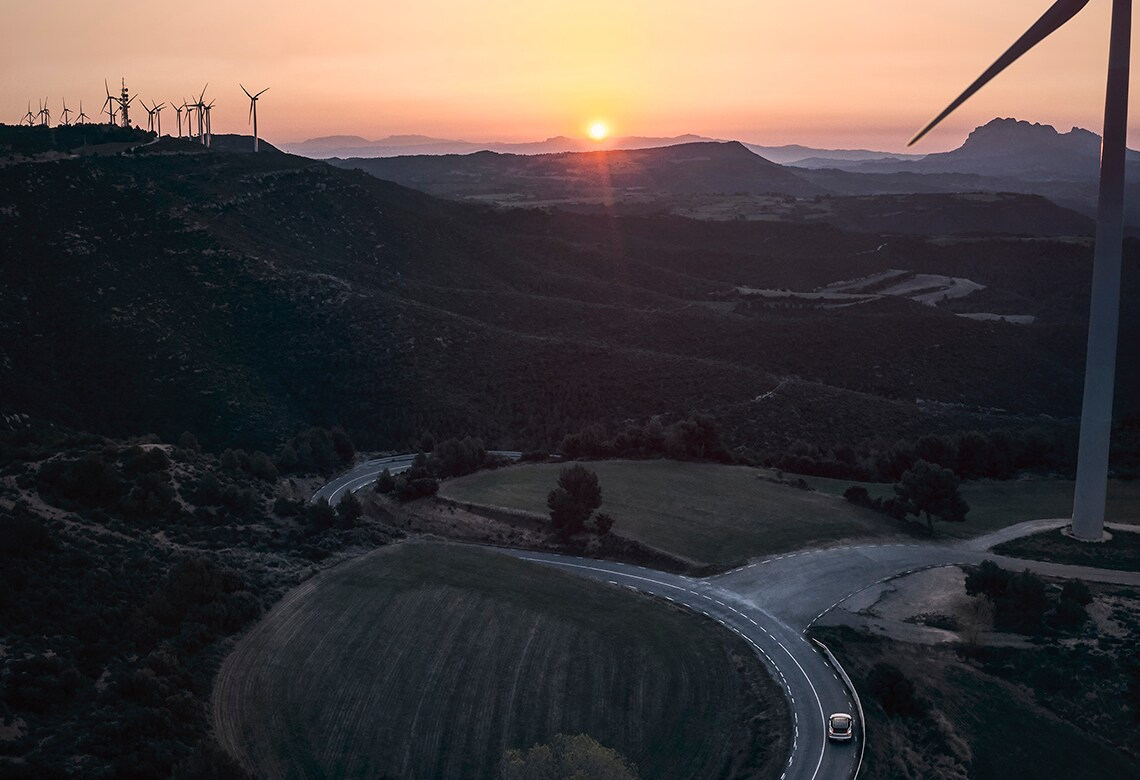 Landscape with wind turbines and Volvo car on the road.